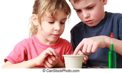 boy and little girl put in pot with soil seed plants, white...