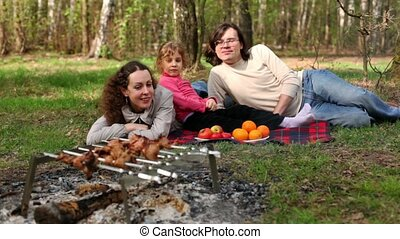 Parents and daugther lay on grass covered by plaid, plates with fruit are near them