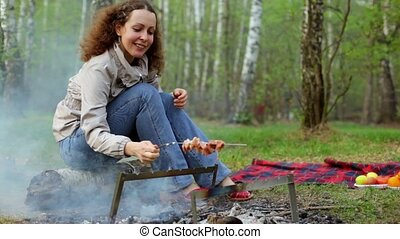 Woman sit and rotate skewer with fresh meat under embers, smoke goes to her and she waves hands, blossom leaves in grove at spring day