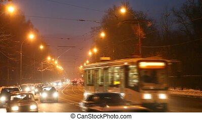 many cars and tram go at night on winter roads to blizzard