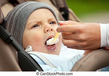 Mom feeding one-year old boy sitting in stroller