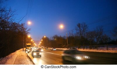cars and truck moves in night on winter, shined road