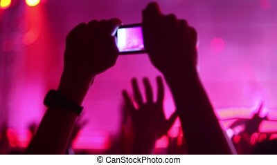 Hands hold camera with digital display among people at rave party