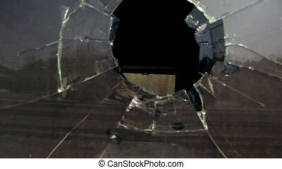 Motion inside hole in broken window at railcar, dark...