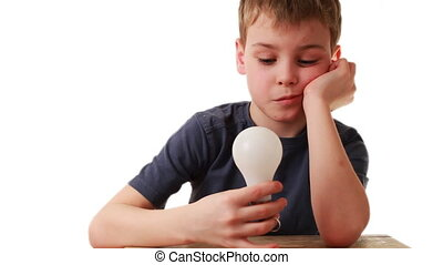 boy holds in hand light bulb that miraculously lights, he is...