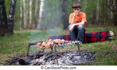 Boy sit on log and drink juice, meat cooking on embers
