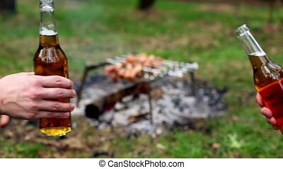 Two hands clink bottles with beer twice, at background of kebab on bonfire