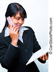 Side view of young businesswoman having dicsussion on phne