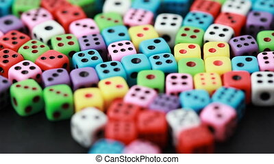 many colorful dice rotate on black background, close-up