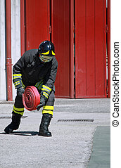 Fireman while unrolls a fire hose to extinguish the flames -...