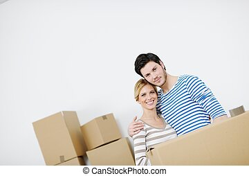 Young couple moving in new house - happy Young couple moving...