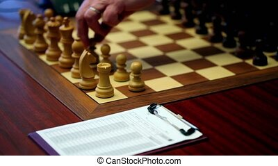Hand arranges figures on chessboard, paper for log moves lay on table