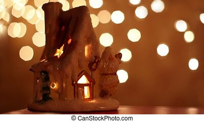 toy house-candlestick stand at background of light spots -...