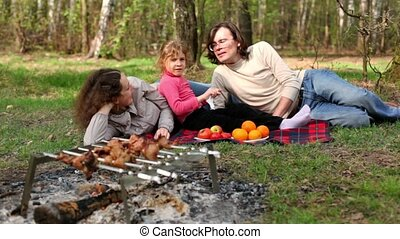 Family lay on grass covered by plaid, plates with fruit are near them