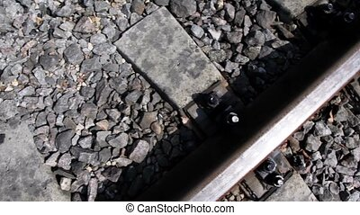 Rails and cross ties of railway among stones, shown in...