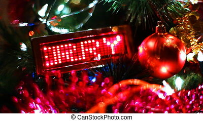 LED display with running line MERRY CHRISTMAS among of blinking garlands and toys on New Year tree