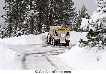 Snow Plow - A large snow plow clearing a parking lot and...