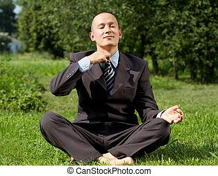 Businessman Meditating Outdoors - Man businessman meditating...