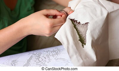Needlework - Woman hands doing cross-stitch A close up of...