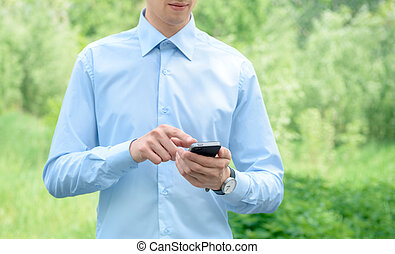 Businessman with mobile phone - Young businessman using...