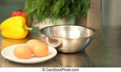 The cook breaks eggs in a bowl