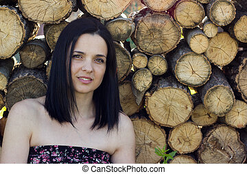 Woman in front of logs