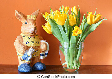 Happy Easter - Fresh yellow tulips blossoming in a glass...