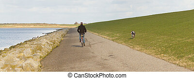 A cyclist with his dog on a dutch dike