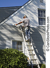 Man Painting House - Man high on ladder painting house with...