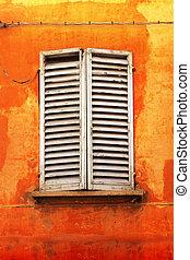 Shutters on orange wall