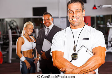 muscular senior gym trainer portrait with colleagues in...