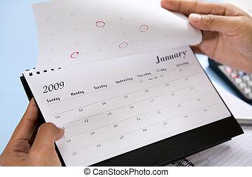 Opening 2009 calendar - Hands flipping the calendar, showing...