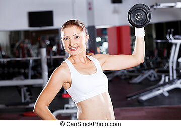 young fitness woman exercising with dumbbell in gym