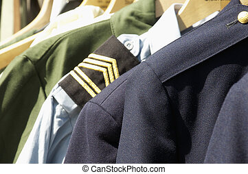 military uniforms hanging on hangers