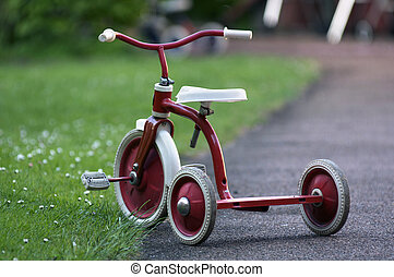 tricycle - a red child tricycle in a garden