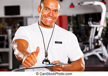 happy male gym trainer giving thumb up