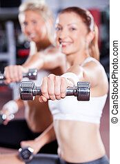 two young woman doing dumbbell exercise