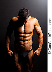 muscular mans body in studio light