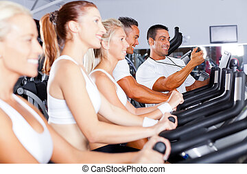 sport coach training cyclists in gym