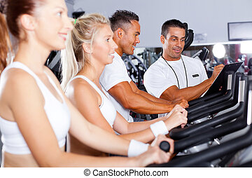 fitness people biking in gym with personal