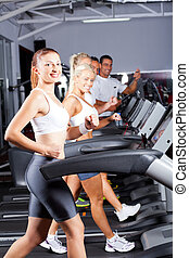 group of fitness people running on treadmill