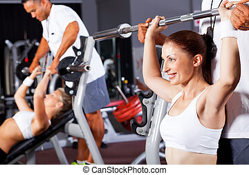 fitness woman with personal trainer in gym
