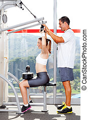 fitness woman in gym with personal trainer