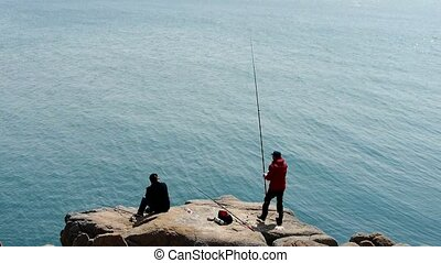 Man fishing on reef.