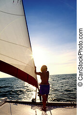 Sailing adventure - A woman on the bow of a sailboat looking...