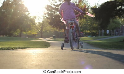 Little Girl Rides Her Bike Up Hill - A cute little Asian...