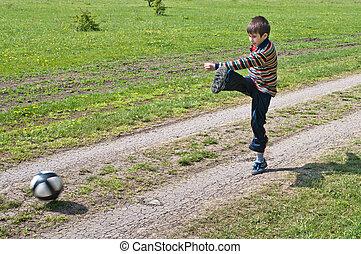 Boy beats kick a soccer ball