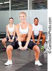 group of people doing fitness exercise with dumbbell in gym
