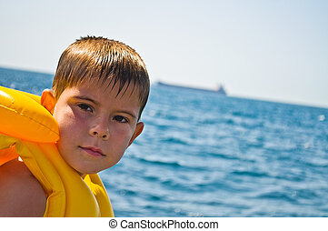 Boy in life jacket, standing in the background of the sea