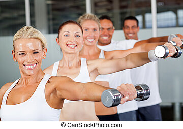 group of people working out with dumbbells
